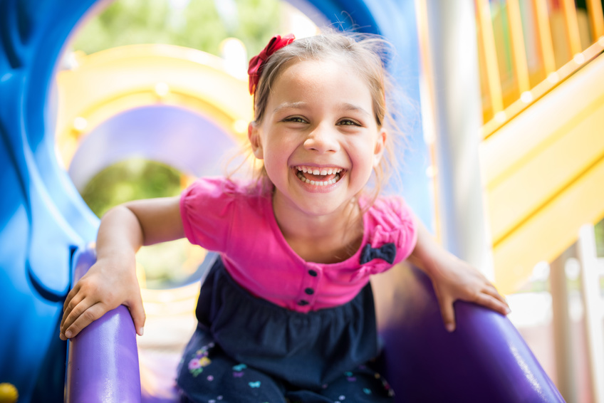little girl playing on purple slide
